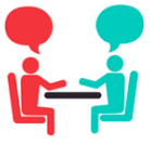 Image of two people sitting together at a table talking