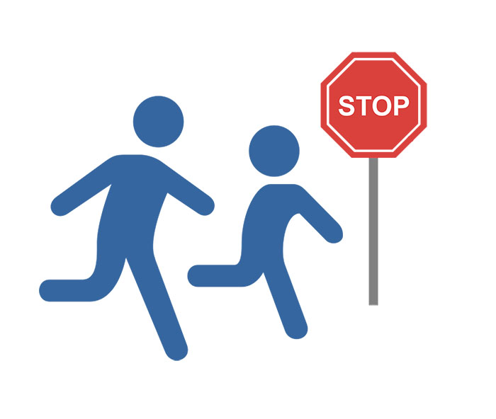 Image of a child running past a stop sign with parent right behind them.